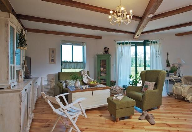 Relaxační část otevřeného prostoru s hezkým výhledem do okolí. Venkovský ráz interiéru podtrhuje vedle kredence i truhla použitá jako stolek a dřevěné stropní trámy. Jemnost vnášejí bílé plátěné záclony a nezbytný kočárek s panenkou - jedna z nejoblíbenějších hraček vnučky Šarlotky.